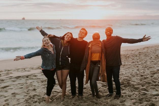 Amis heureux profitant de la plage au coucher du soleil