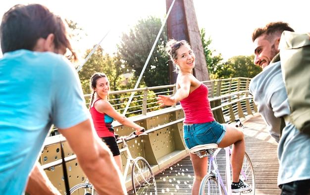 Amis heureux s'amusant à faire du vélo au parc de la ville