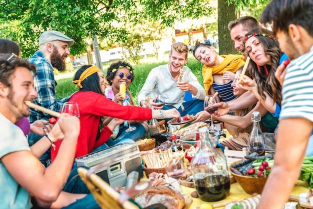 Amis heureux s'amuser en plein air manger une collation et boire du vin rouge au pique-nique barbecue