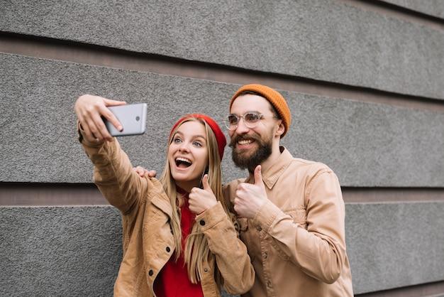 Amis hipster positifs et souriants prenant des selfies ensemble, montrant le coup