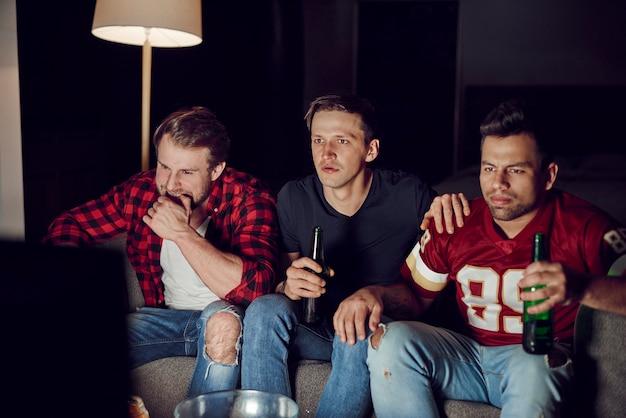 Amis hommes regardant le football américain le soir