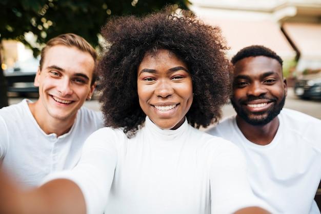 Amis interculturels souriant pour la caméra