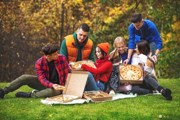 Amis jeune drôle belle profiter de la pizza et socialiser sur un pique-nique dans la nature