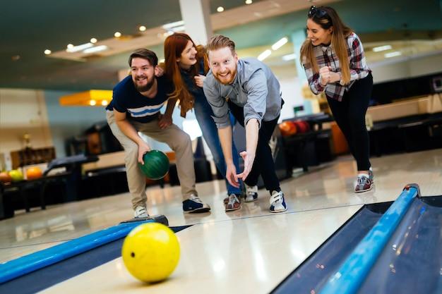 Amis jouant au bowling au club et s'amusant à jouer avec désinvolture