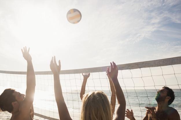 Amis jouant au volleyball de plage