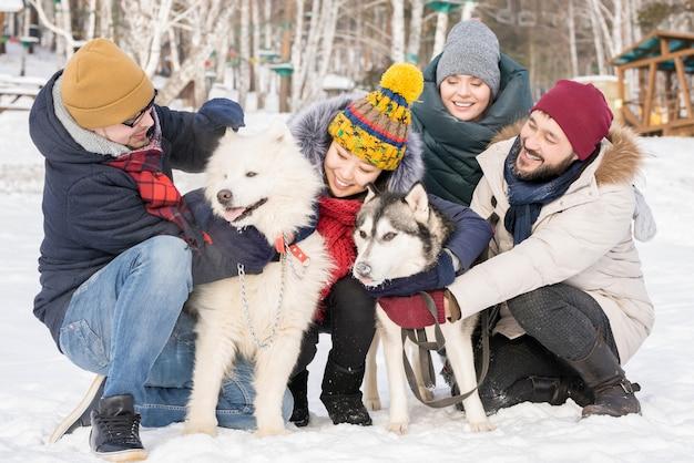 Amis jouant avec des chiens dans la neige