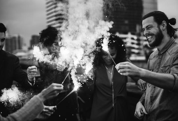 Amis jouant avec des feux de bengale à l'extérieur