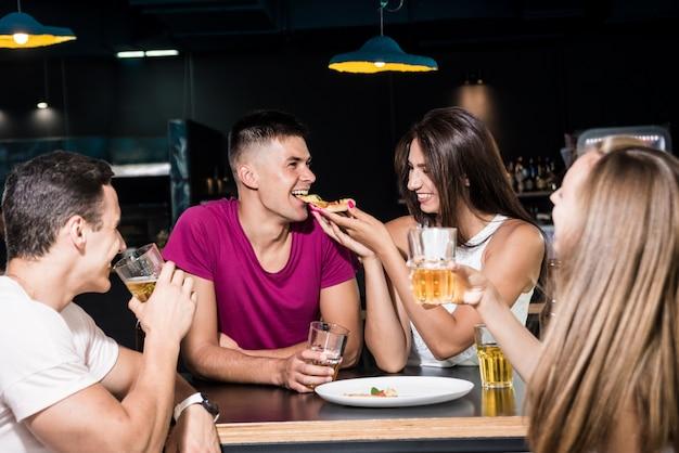 Amis joyeux dans le pub. boire de la bière, manger de la pizza, parler, s'amuser.