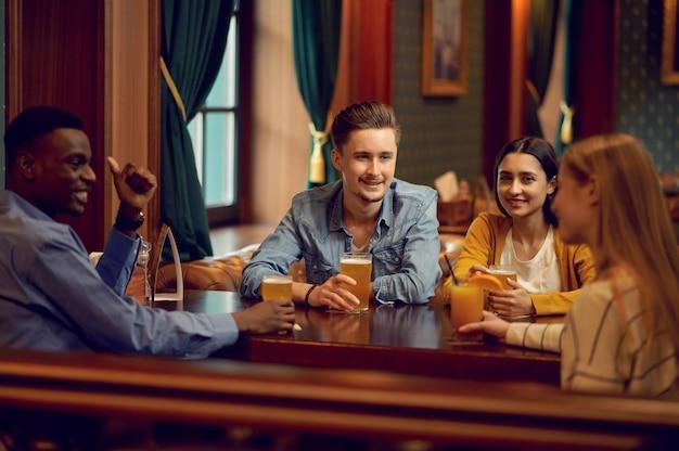 Des amis joyeux trinquent au comptoir du bar. groupe de personnes se détendre dans un pub, mode de vie nocturne, amitié, célébration de l'événement