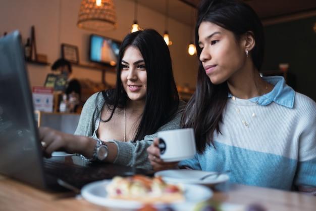 Amis latina qui étudient ou travaillent sur leur ordinateur portable dans un bar.