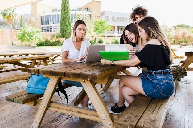 Amis, lecture de manuel et en utilisant un ordinateur portable à table