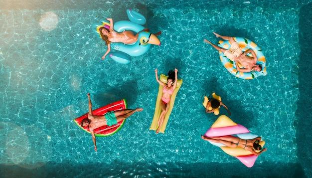 Amis en maillot de bain dans la piscine bronzant