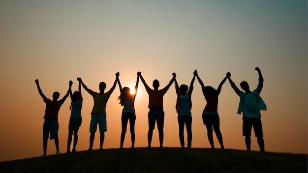 Amis, main dans la main au coucher du soleil
