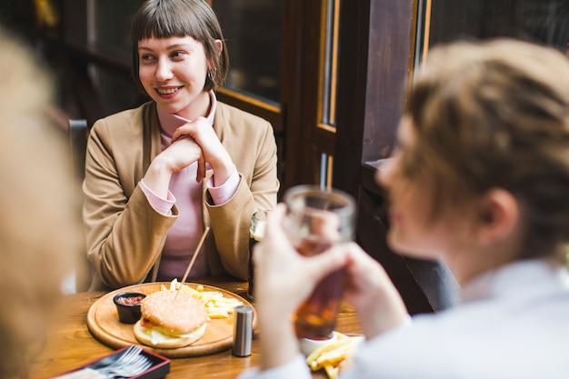Amis mangeant et conversant au restaurant
