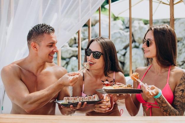 Amis mangeant ensemble des rouleaux de sushi au bord de la piscine