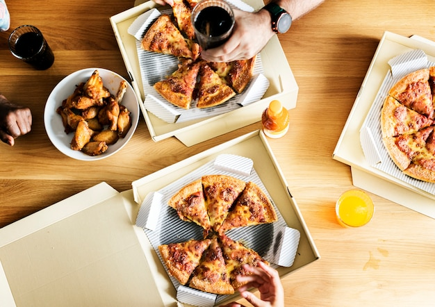 Amis mangeant une pizza ensemble à la maison