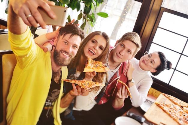 Des amis mangent une pizza dans un café, sourient et se tirent dessus dans le smartphone de l'appareil photo