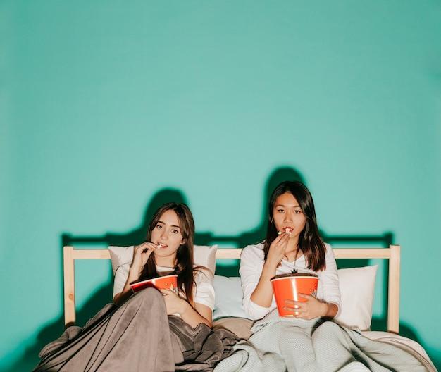 Amis, manger du maïs soufflé sur le lit