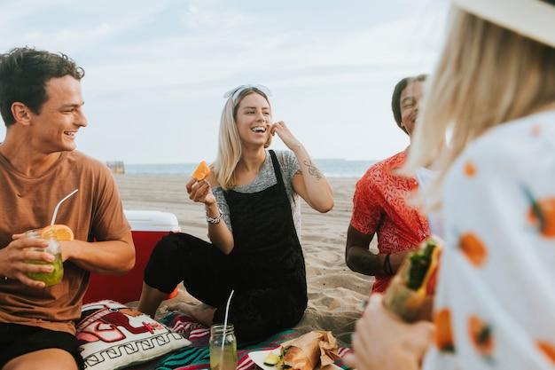 Amis, manger de la nourriture lors d'un pique-nique à la plage