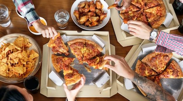 Amis, manger des pizzas ensemble à la maison
