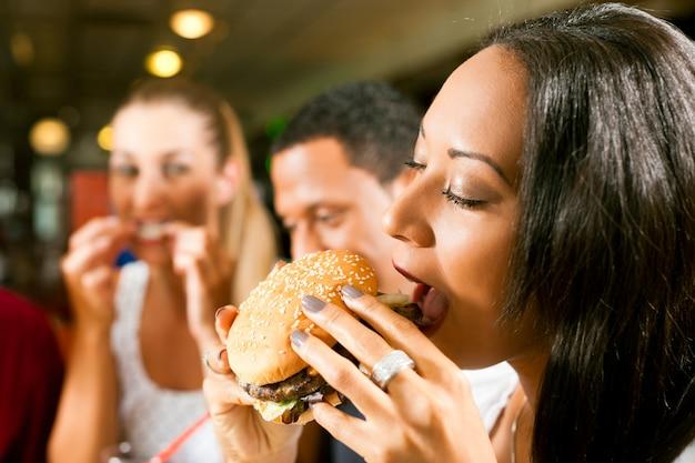 Amis, manger de la restauration rapide dans un restaurant