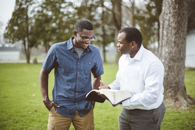 Amis masculins afro-américains debout dans le parc et discuter de la bible
