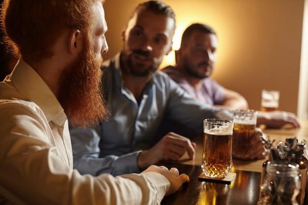 Amis masculins ayant une bière au bar