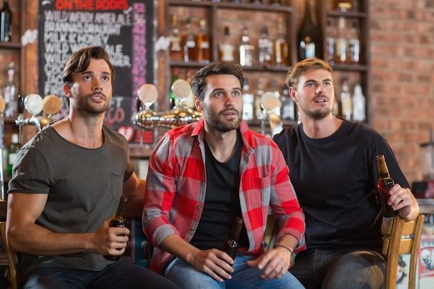 Amis masculins choqués à la recherche de suite tout en tenant des bouteilles de bière
