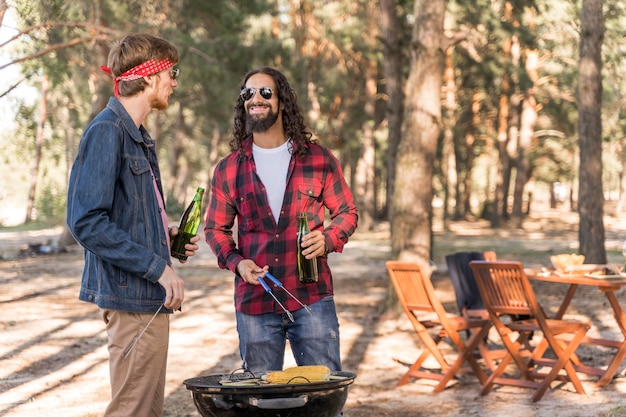 Amis masculins conversant autour de la bière et barbecue