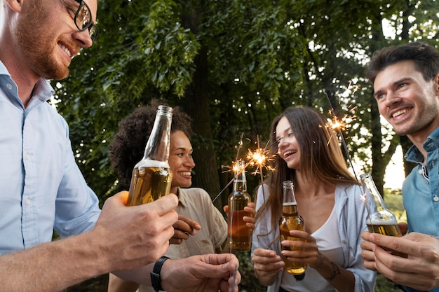 Amis masculins et féminins passant du temps ensemble à l'extérieur et buvant de la bière