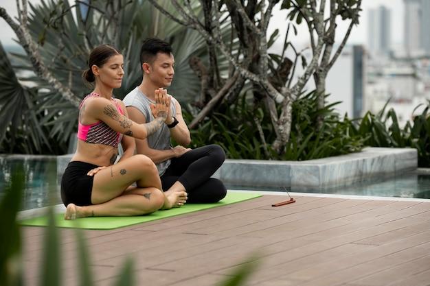 Amis masculins et féminins pratiquant le yoga