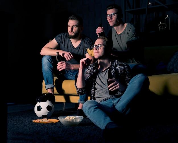 Amis masculins regardant le sport à la télévision ensemble tout en ayant de la bière et des collations