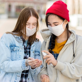 Amis avec masque à l'aide d'un désinfectant pour les mains