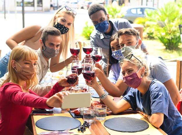 Amis avec masque facial prenant selfie tout en grillant du vin rouge au restaurant - les jeunes s'amusant avec des boissons - le nouveau concept de mode de vie normal
