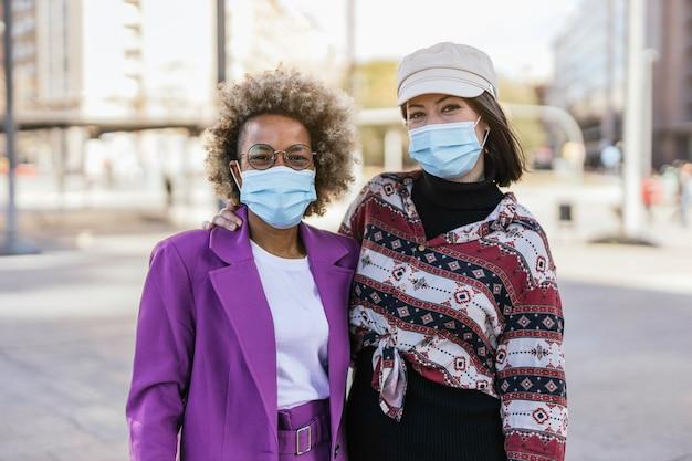 Amis avec des masques de protection dans la rue