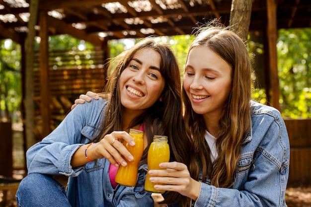 Amis à mi-tir avec des bouteilles de jus de fruits frais