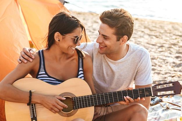 Amis mignons aimant couple en plein air sur la plage assis tout en jouant à la guitare