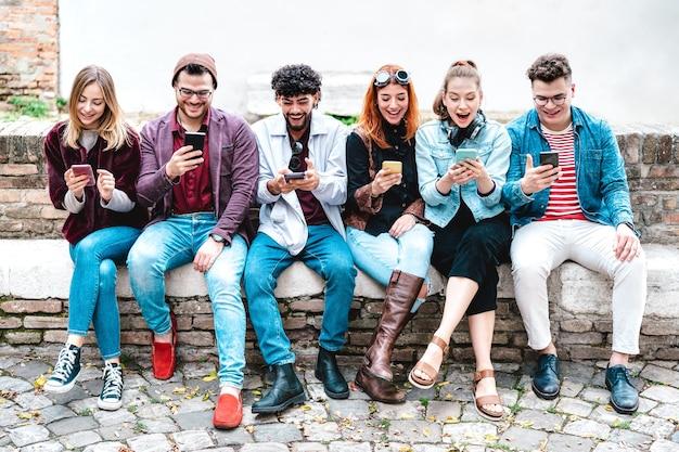 Amis milenial heureux utilisant le smartphone à la pause d'université