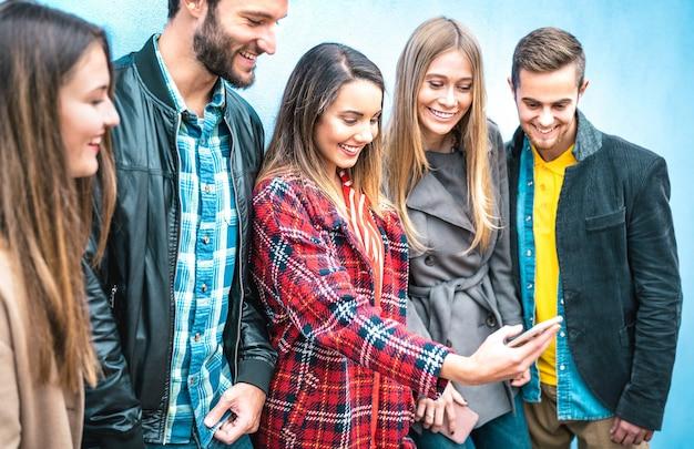 Amis millénaires sur un moment accro à l'aide de téléphones intelligents mobiles