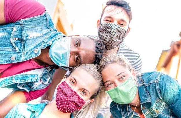 Amis millénaires multiraciales prenant selfie souriant derrière des masques