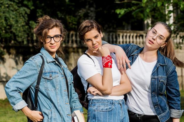 Amis à la mode debout ensemble dans le parc