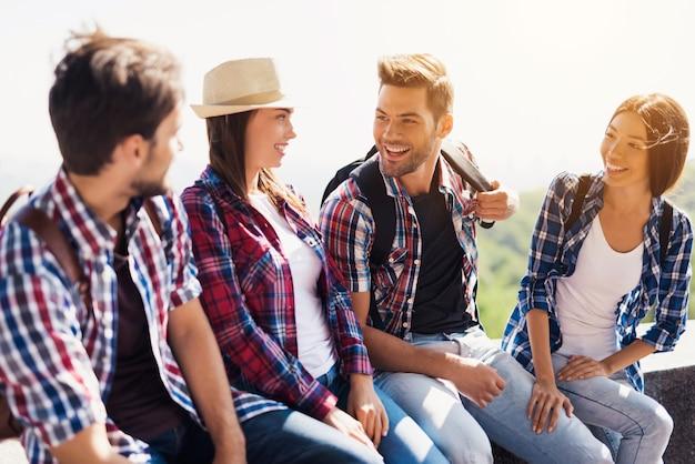 Les amis multi-raciaux touristes sourient parlent rire.