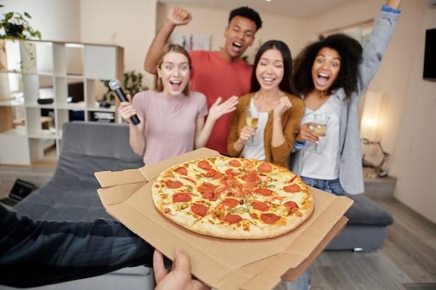 Des amis multiculturels excités par de délicieuses pizzas ont eu une pizza fraîchement préparée lors d'une soirée karaoké