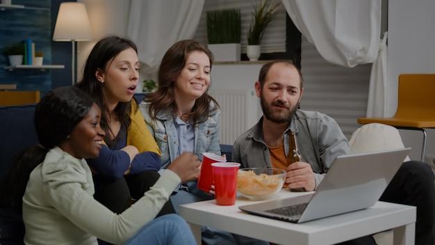 Amis multiethniques assis sur un canapé ayant une réunion par vidéoconférence en ligne