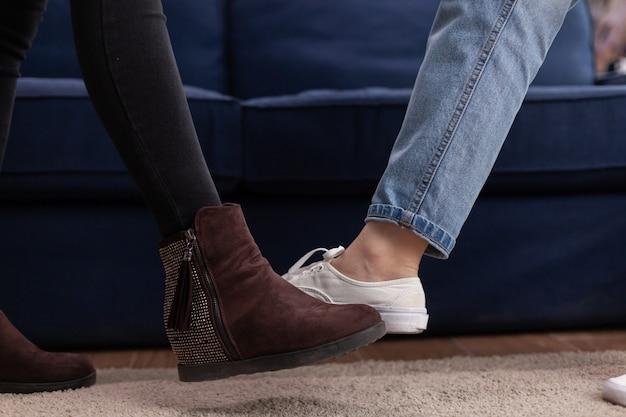 Amis multiethniques disant bonjour toucher les pieds en gardant une distance sociale, par mesure de sécurité pendant la pandémie sociale avec le coronavirus, célébrant les amis à la hanche dans le salon.