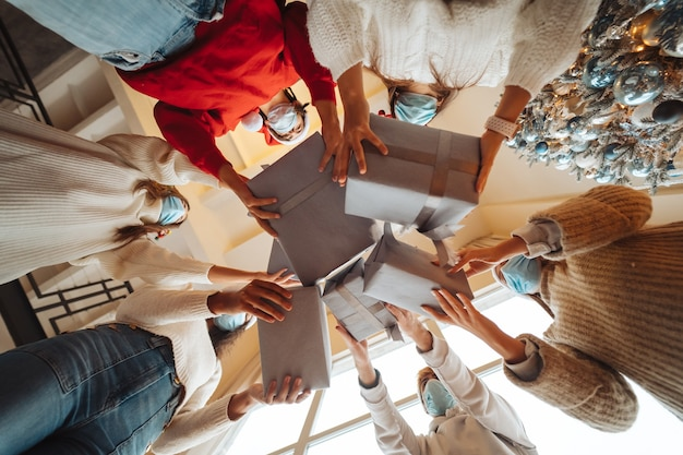 Des amis multiethniques jetant leurs cadeaux de noël en l'air