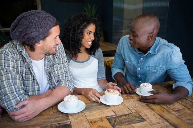 Amis multiethniques parlant tout en prenant un café à table dans un café