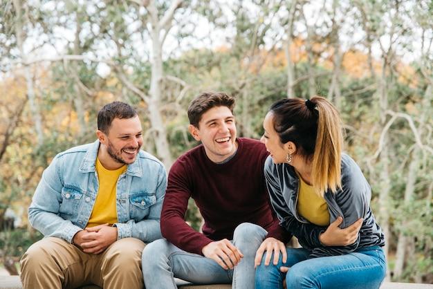 Amis multiethniques racontant des histoires drôles et assis dans un parc