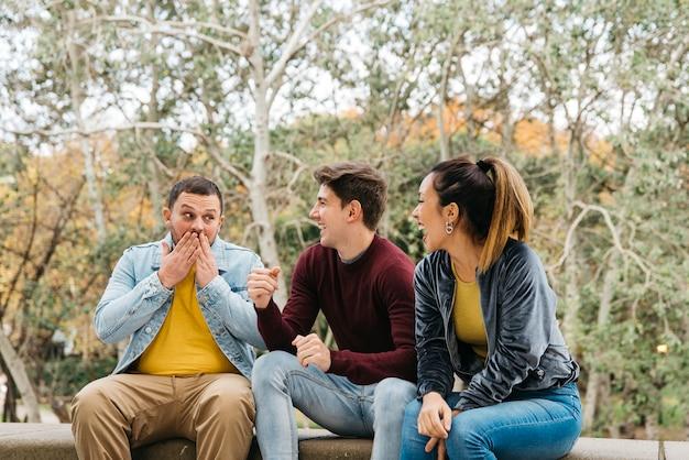 Amis multiethniques s'amusent assis dans la nature
