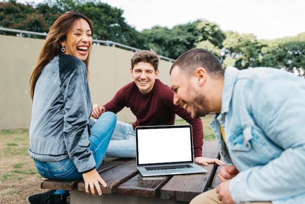 Des amis multiethniques s'amusent dans un parc avec un ordinateur portable